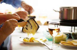 Une personne se sert le fromage fondu de sa raclette. Un verre de vin blanc sur la table.