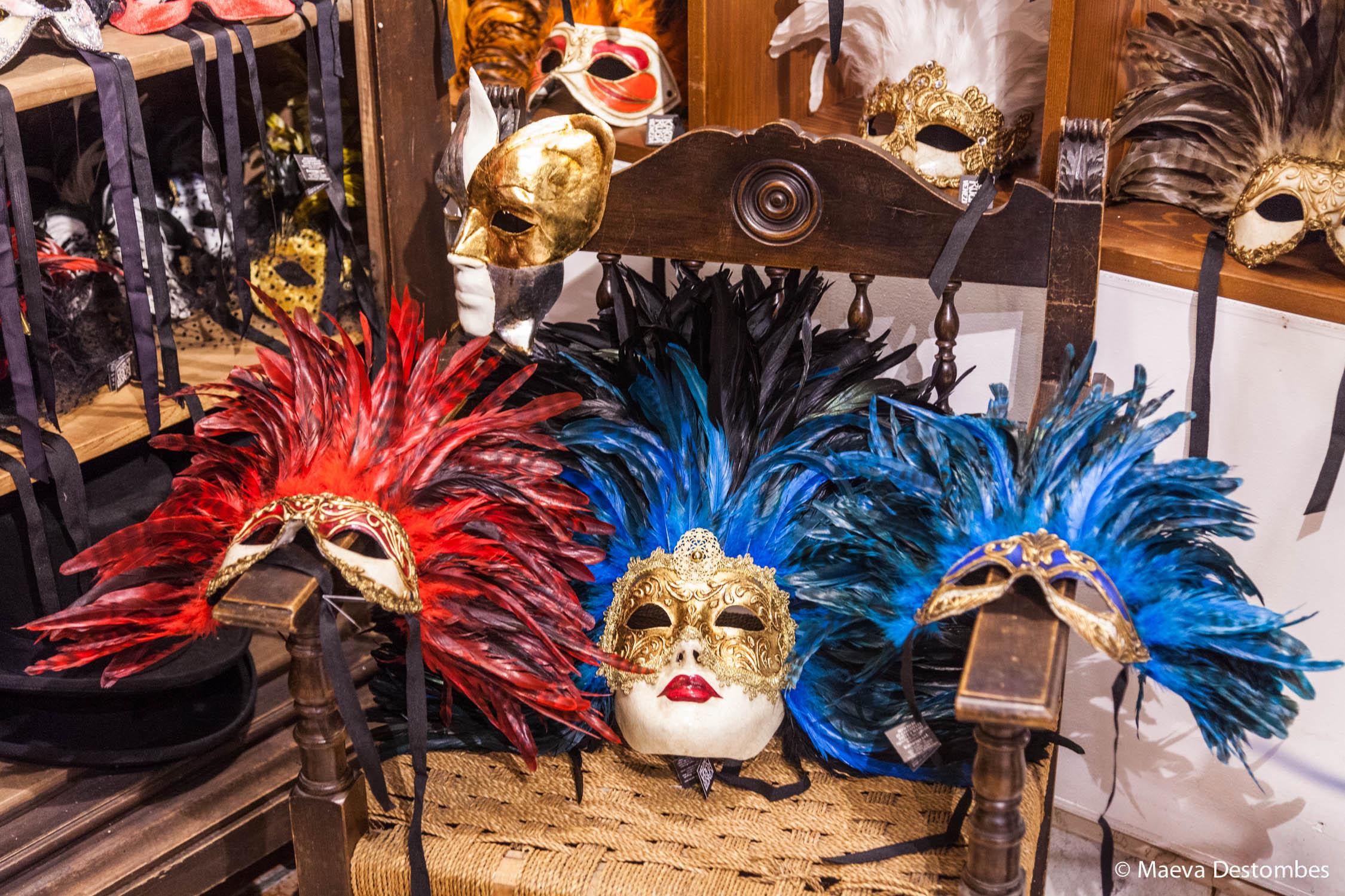 Des masques à plumes posés sur une chaise dans une boutique au carnaval de Venise