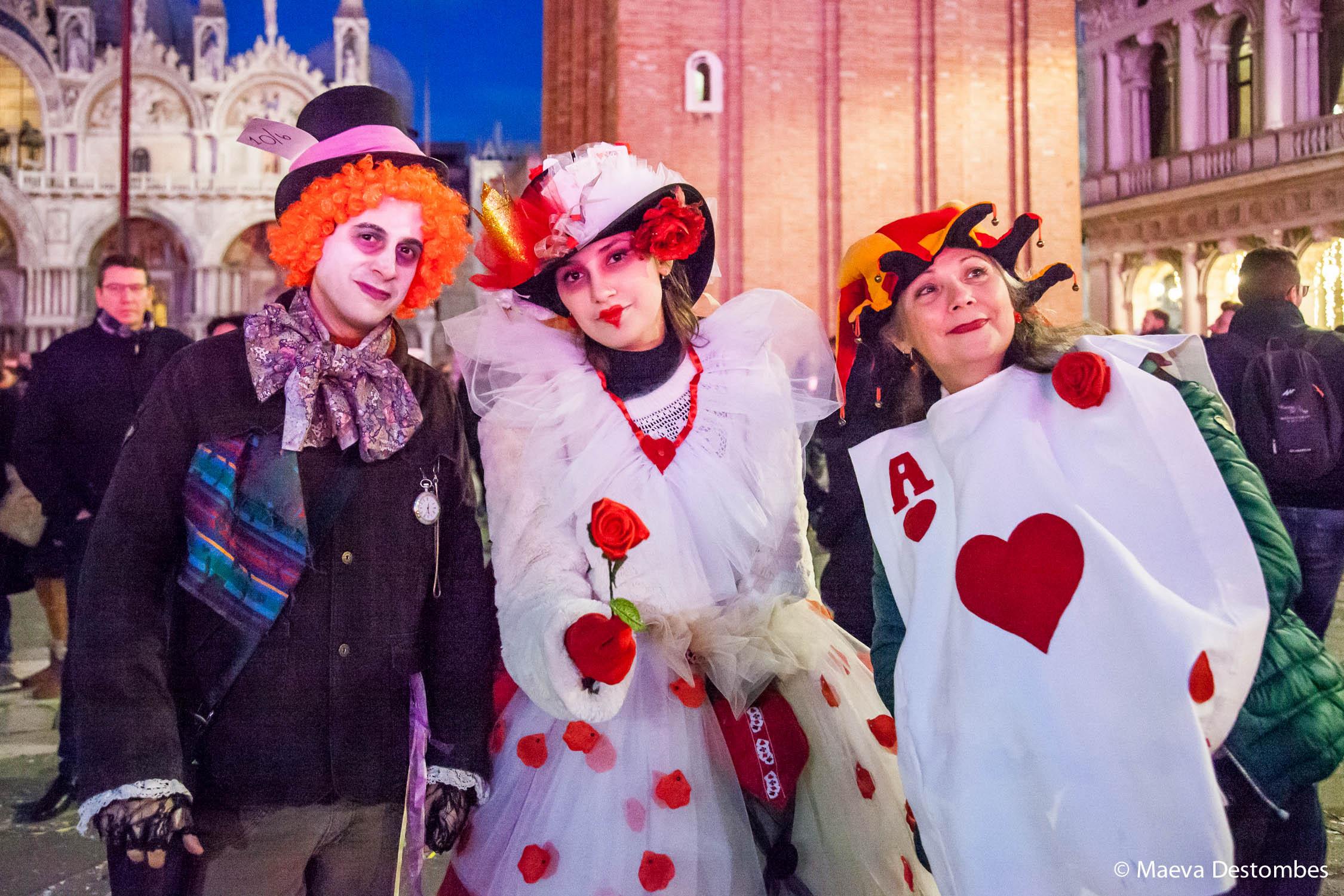 Trois personnes déguisées sur le thème d'Alice aux pays des merveilles lors du carnaval de Venise
