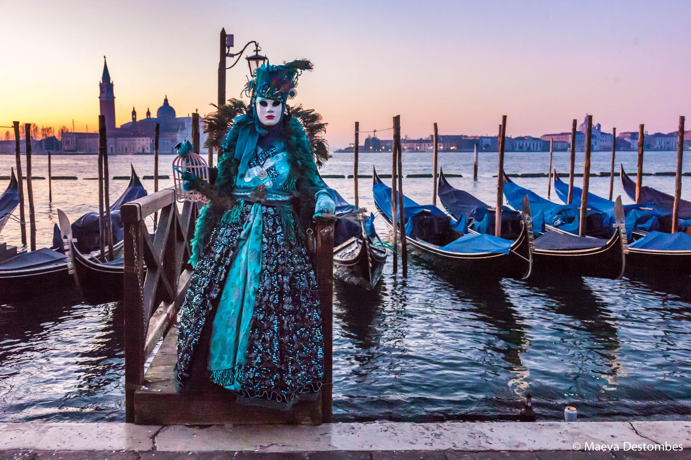 Un carnavalier en costume au bord de la lagune lors du carnaval de Venise