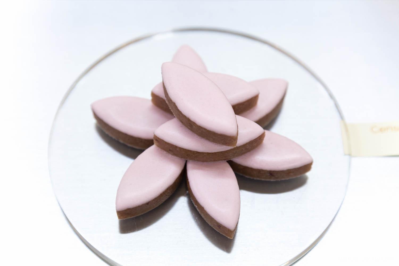 Neuf calissons d'Aix-en-Provence dont le glaçage est rose sont rangés et entassés en rosace.